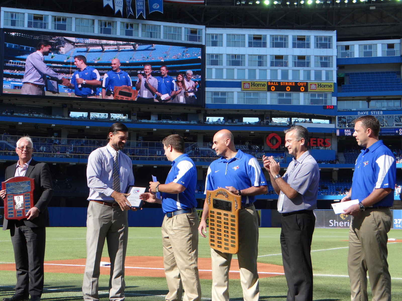Fourth-year Sheridan student and Blue Jays' Scholarship Award winner, Dan Hilborn, is presented with a plaque by team orthopedic surgeon Dr. Jason Smith during pre-game ceremonies at Rogers Centre on Saturday.