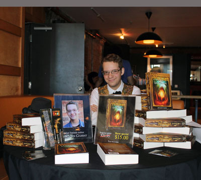 Benjamin Gabbay, 17, sits behind the display for his novel, Wingheart: Luminous Rock. The book is the first installment in a trilogy. As he waited for people to approach his table, he typed. He is writing the second book in the Wingheart trilogy, out next fall. The trilogy is published under his family's company, Arkane Books. Gabbay launched the book in 2012 at The Word On The Street Festival, where he will again be attending on Sept. 22. http://arkanebooks.com/index.html
