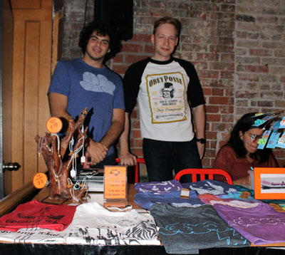 "Vasilis Glezakos and Chris Tsoutsoulas stand behind their table at the Indie Arts Market. Their product is t-shirts, designed and created by Glezakos under the name, Pass the Soap. ""He's the art master, and I'm more the business side,"" said Tsoutsoulas, referring to Glezakos. The ideas for the shirts usually come to Glezakos in dreams. The duo has been setting up their merchandise tables at hip-hop and breakdancing event, as Glezakos is a participating member of that community. This is the first time they've attended the market.   http://www.passthesoap.ca/"