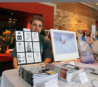 "Claudio Ghirardo sits at his table with comic books and his art on display. This is his second time participating in the Indie Arts Market. ""I haven't sold anything yet, but you never know,"" said Ghirardo. ""I did pretty well at the last one."" Ghirardo also produces the webcomic, Untitled.  http://paintedcomic.wordpress.com/"