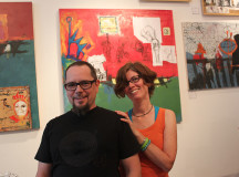 The husband and wife team standing in front of their work at their Saturday exhibit.