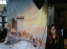 Photography student Mikaela Baker sits next to the 18% Grey Club's photo-op backdrop.