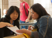 Wendy Lin asks Molly Kwan for directions to her Travel and Tourism class at the info booth in B wing.