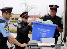 Police Constables Mike Semple, Rose Ferraro, and Staff Sergeant Gerry Harnden loaded the Eden Community Food Bank truck with donations.