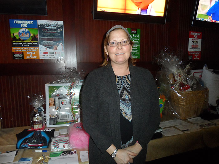 Kimm stands in front of one of the fully loaded raffle prize tables at the Milton Shoeless Joe's fundraiser.