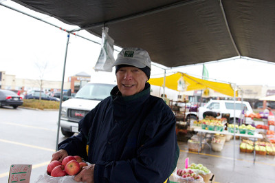 Doug Guthrie, manager of the Oakville Civitan Club's farmers' market, holds up a bag of apples for sale at the Roberts Farm's booth on Saturday. Guthrie has been managing the market since 1999.