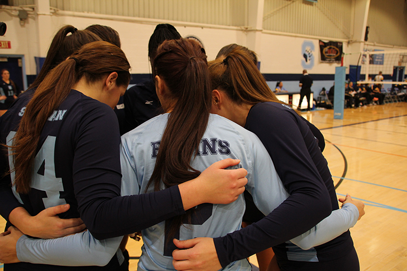 The women's volleyball team huddles