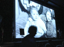 Marguerite Elias Thon returns to her seat while a picture of herself and her sister before the Nazis invaded France is displayed