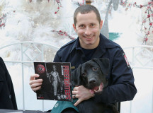 "Oakville firefighter Allan Kiss poses with Déja, a dog guide in training. Kiss is on the back page of the charity calendar the Oakville firefighters are selling. ""It was an opportunity to work with the dog guides in a fun way to raise some money."" The firefighters will have a booth set up in Oakville Place Mondays Dec. 2, 9 and 16."