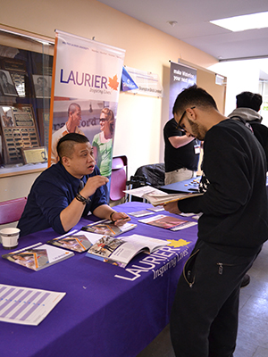 Third-year Business Administrating - Marketing student, Sumer Haj-Ali, 20, talking to a Laurier University representative at the Davis campus.