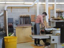 Wood working student chips away at a table saw