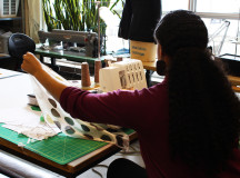 Textile student works away at fabric