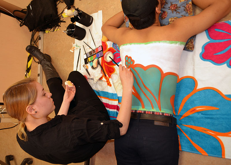Isabelle Bertraud recreates a flowered pattern on Scott Goe's back.