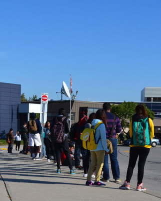 A lineup of people waiting for the Sheridan shuttle at the Trafalgar Campus during peak hours.