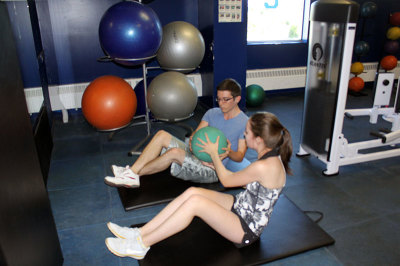Amy Cannon and Colt Nicostrio passing the medicine ball back-and-forth at Trafalgar campus' gym