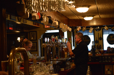 A bartender serves patrons at The Queen's Head, in downtown Oakville.
