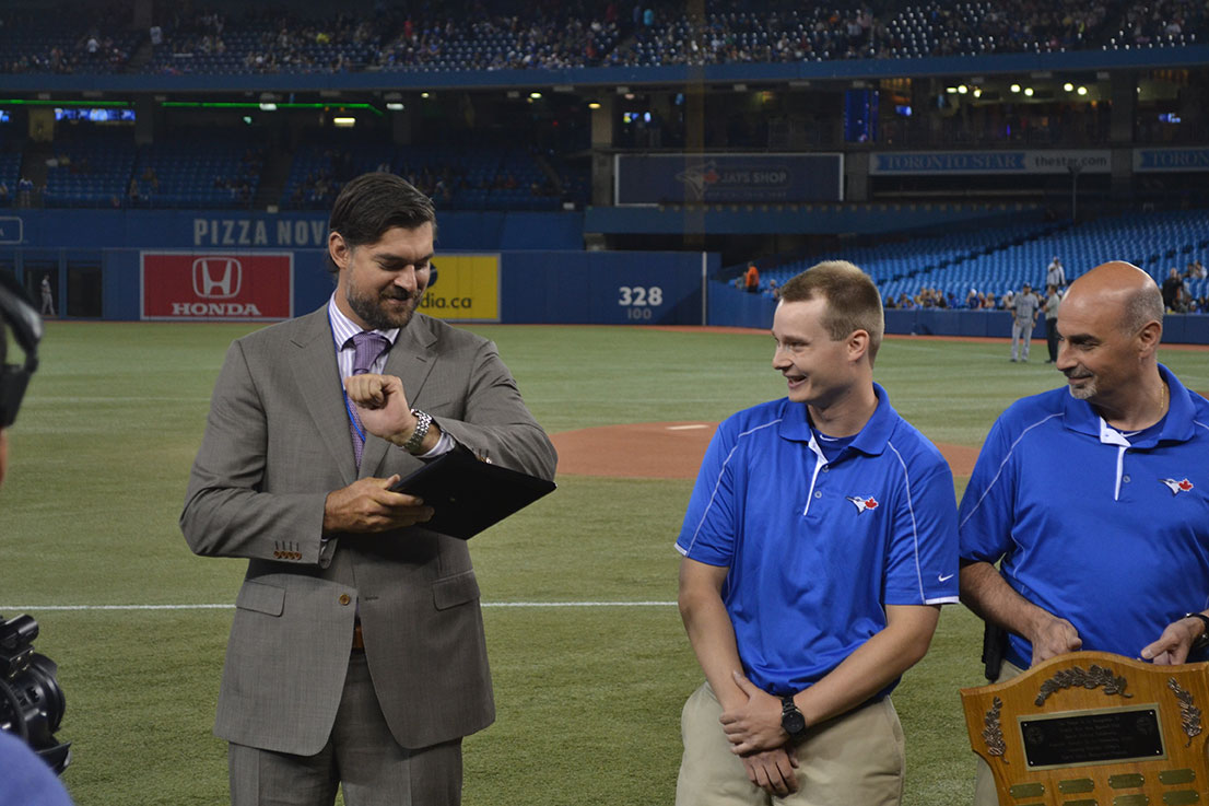 Dr. Jason Smith shines up the Blue Jays Award before handing it to Tommy Kratky