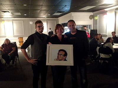 Liam Goodman, left, illustrated and donated the print of Robin Williams being awarded to the participant.
