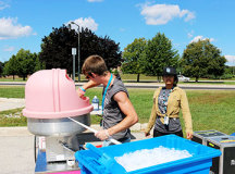 Chris Berwick tends to the Cotton candy while Divya Mehta, 18, scoops snow cones.