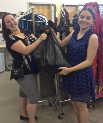 Sarah Read and Morgan Squibb lift up their heavy haul of clothes and accessories they found at the Sheridan Theatre Wardrobe Sale.