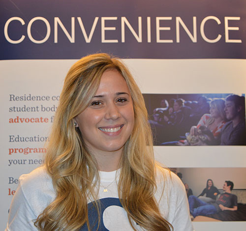 Residence coordinator, Ally Paul, stood behind her booth where she gave prospective students and parents information about residence and organized tours of the first residence building.