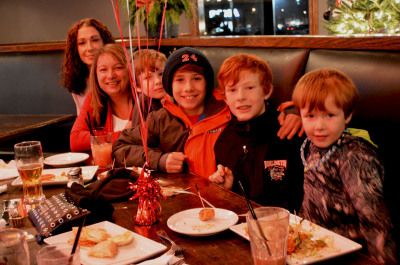 Lisa Savarie and Michelle Halliwell pose behind a table at Drafted with their children during the opening day.