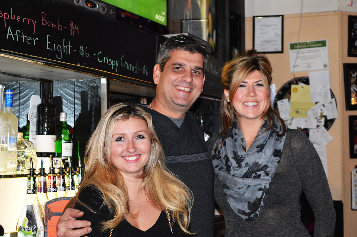 The owner of Shakers, Tony Coelho, stands with two of his employees behind the bar.