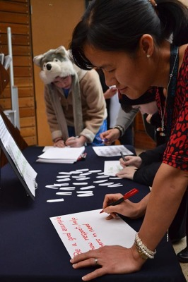 People come to write down their pledge of what they will do to help stop violence against women.