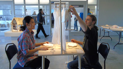 Ceramic Design students Queenie Xu and Jordan Scott try out the texting table at the exhibit.