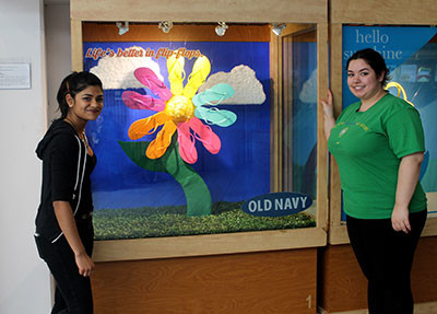 Chelsea Kumar and Laura Katergos pose with their finished window