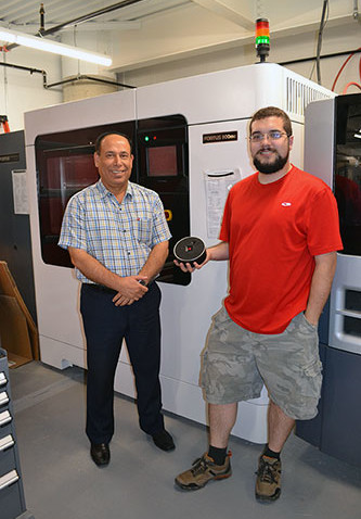 Ryan Vieira, holds up the third version of their audible hockey puck, while standing next to mentor and advisor Amir Alfalahi, in front of the Fortus 900, the machine they used for most of their 3D printing.
