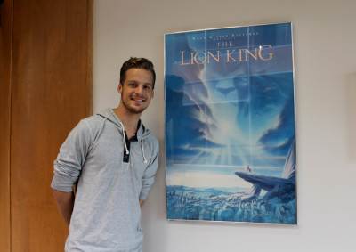 Morin stands in the Sheridan hallway next to the Lion King poster.