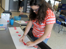 Volunteer Dima Kukje Zada taping hearts to a string for display. ( Photography by Courtney Blok / The Sheridan Sun)
