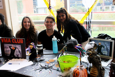 Jasmine Monk, Brett Wilson, and Chelsea Kumar, members of the Visual Merchandising Club pose in front of their table.