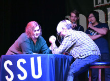 Sheridan students, Victoria Vale, and Liah Wallace, arm wrestle to win $5 off a meal at the Marquee, while announcer Xin Zhang, comments on the action.