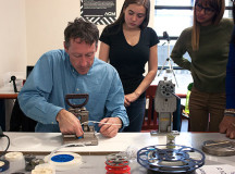 John Kneller, a professor in Sheridan's Bachelor of Film and Television program, demonstrates to students how to splice strips of film together.