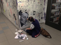 Meghan Judd sits in the hall, adding her work to the wall