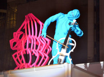 A pink creature stands next to the blue ninja while it serenaded the crowd with the beautiful music of the cello.