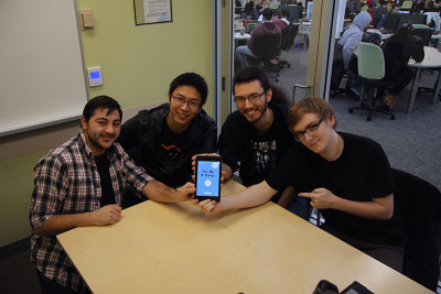 "Winning members of the digital game team show off their complete app ""Tell me a Story"" on a tablet. From Left Michael Amato, Chen Yang, Jesse Sponder, and Brennan McNamara"