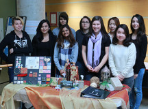 Stacey Torok, Angela Valdez, Victoria Rolfe, Chelsea Kumar, Lisa Zapotoczny, Michelle Garrow, Mya Kim, Cimy Chen and Melanie Berube standing over the Asian display, their creation.