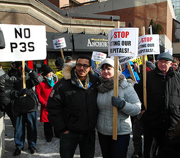 (Ahmad Gaied, executive vice-president of the Ontario Federation of Labour, left, stands with protestors outside of the Sheraton Hotel.) Photo Credit: Jake Hribljan