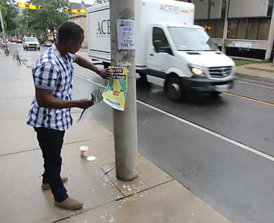 Alex Gendil, a civil engineer from Mississauga and an amateur activist, puts up a poster near the event on Cecil Street, in the riding of federal trade minister Chrystia Freeland.